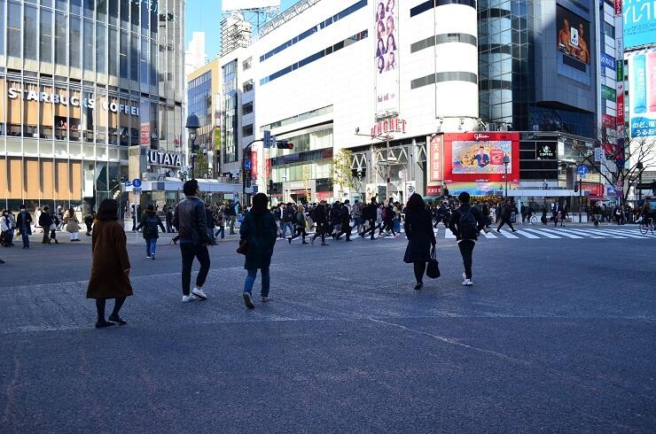 Menschen überqueren die Shibuya Kreuzung in Tokio